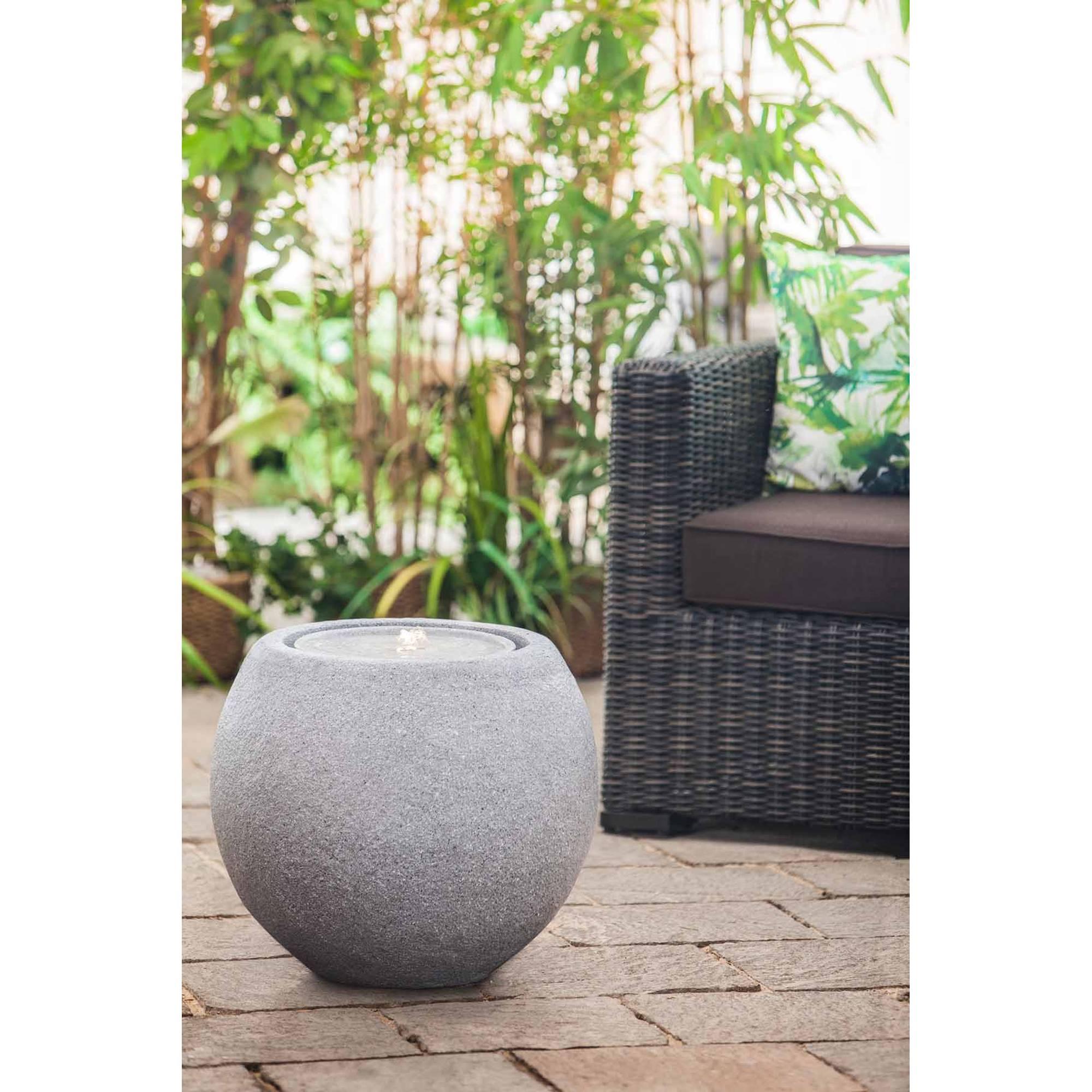 grauer runder Gartenbrunnen auf Steinterrasse vor Gartenstuhl