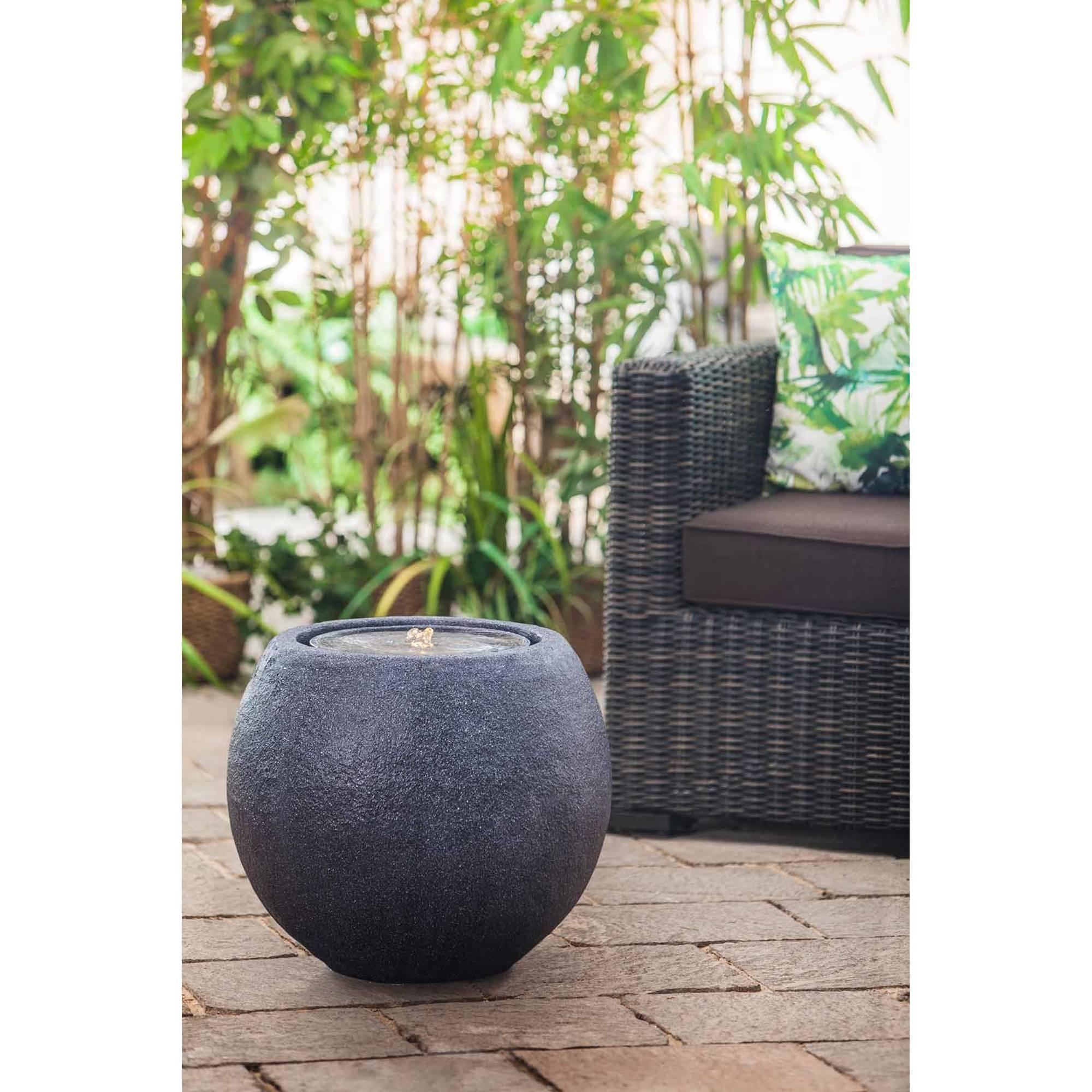 schwarzer runder Gartenbrunnen auf Steinterrasse vor Gartenstuhl