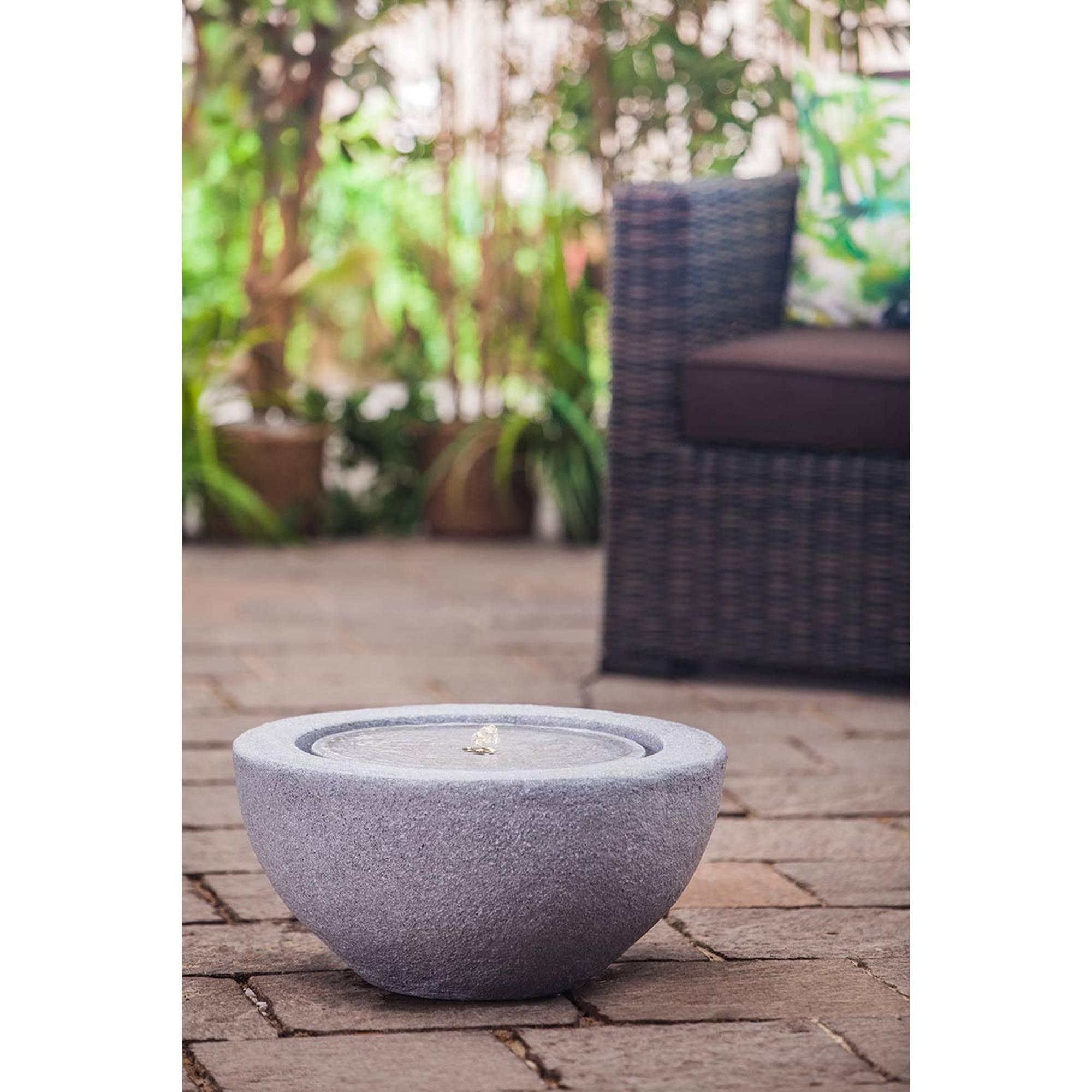 grauer halbrunder Gartenbrunnen auf Steinterrasse vor Gartenstuhl